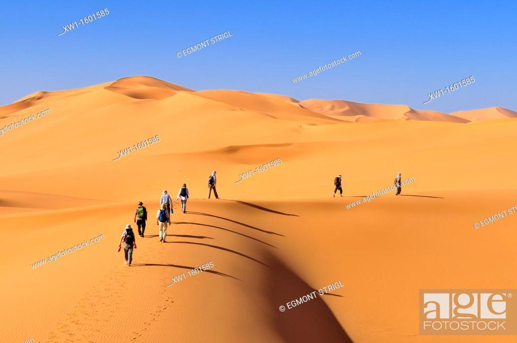 Imagen: group of tourists hiking through the sanddunes of Erg Mehejibad, Ahnet, Algeria, Sahara, North Africa.