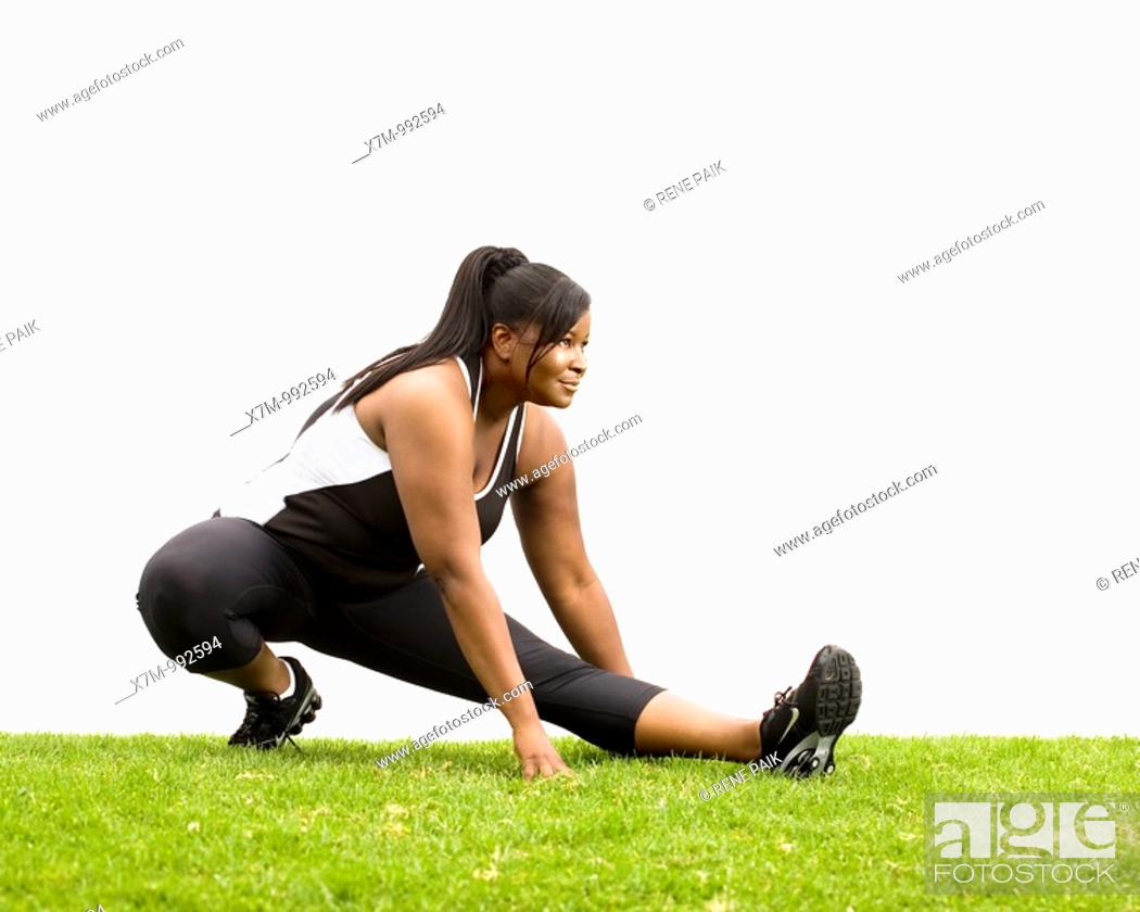 Stock Photo: A black plus size female model plus size model in stretching position.