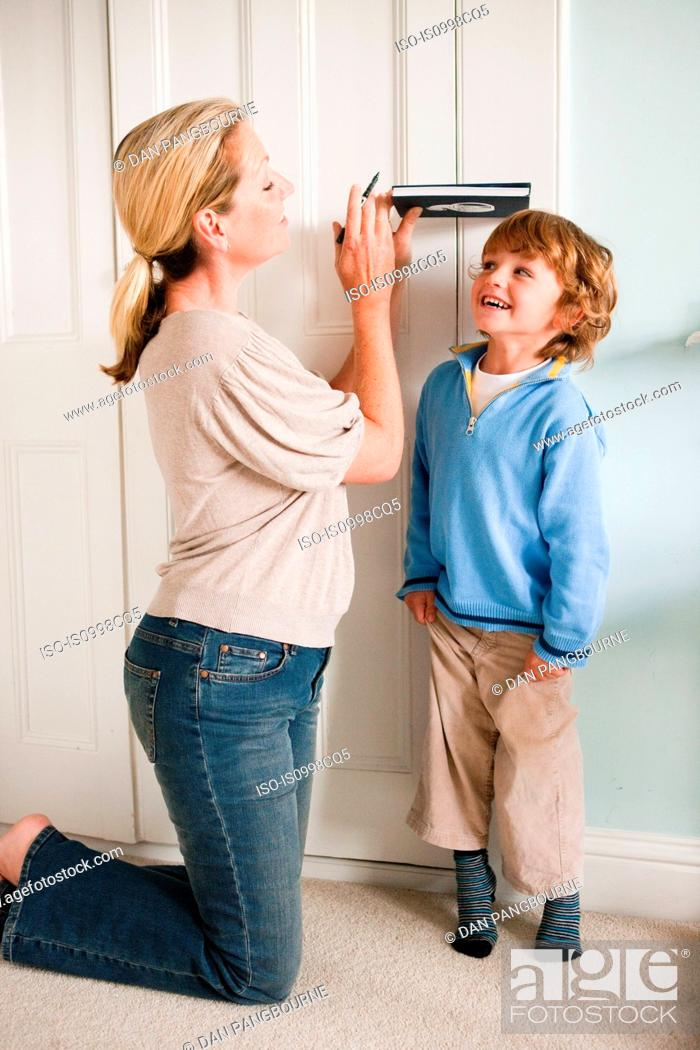 Stock Photo: Mother measuring her son against a door with a book.