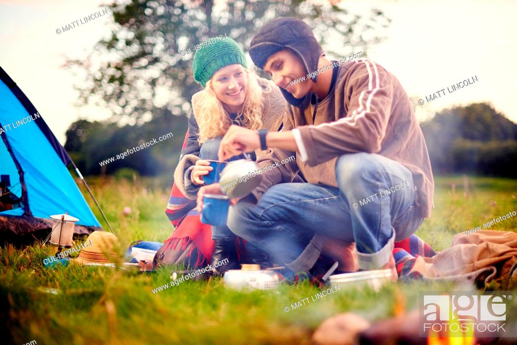 Stock Photo: Young camping couple pouring tea.