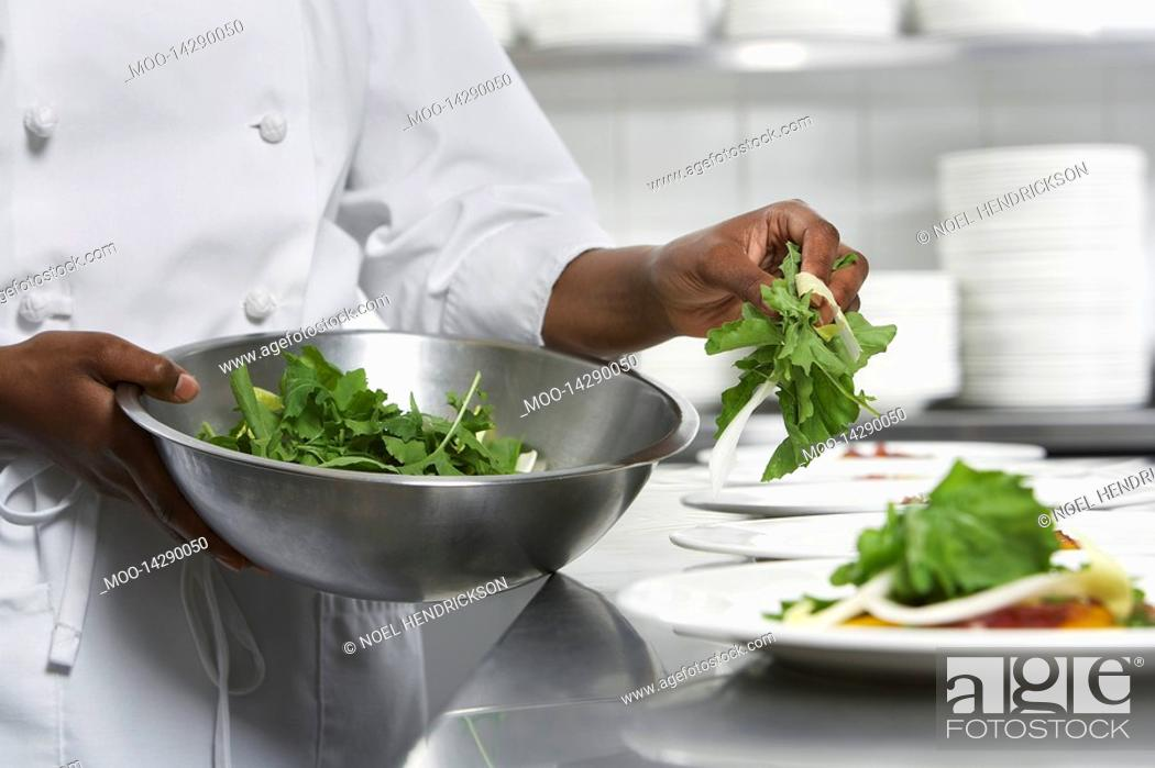 Stock Photo: Chef preparing salad in kitchen mid section.