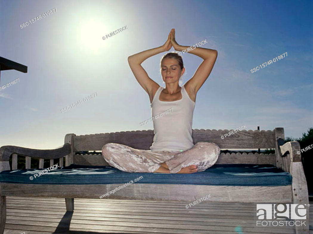 Stock Photo: Young woman practicing yoga on a bench.