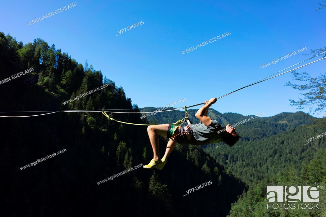 Imagen: young outdoor sportsman climbing on highline slackline over valley in south of Germany, Bavaria, near border to Austria.