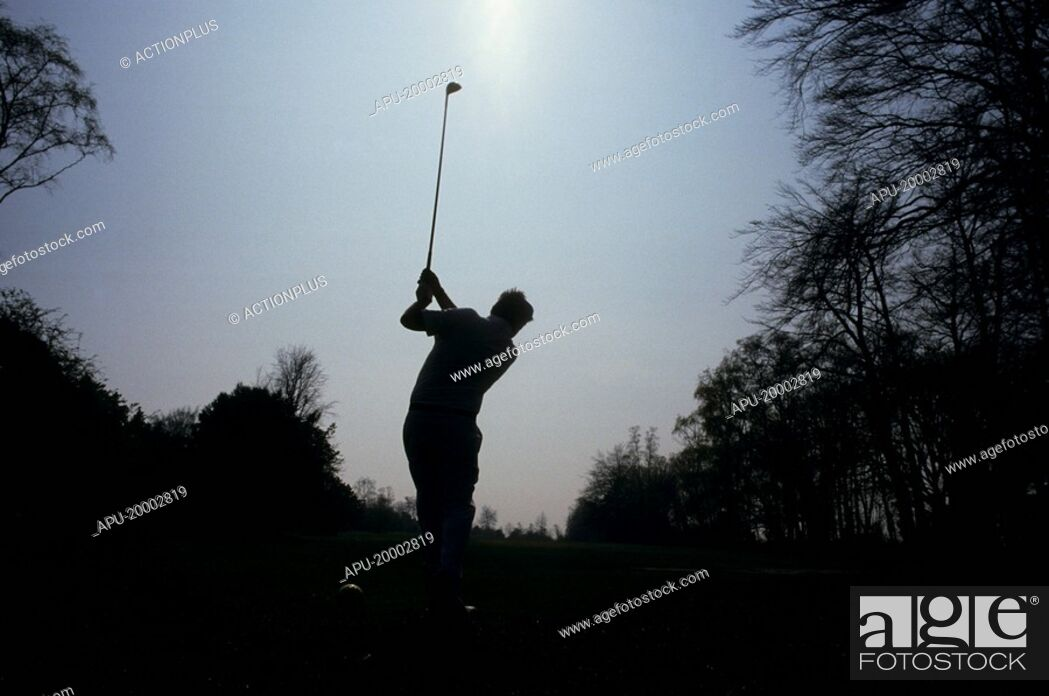 Stock Photo: Silhouette of a golfer tees off on a golf course.