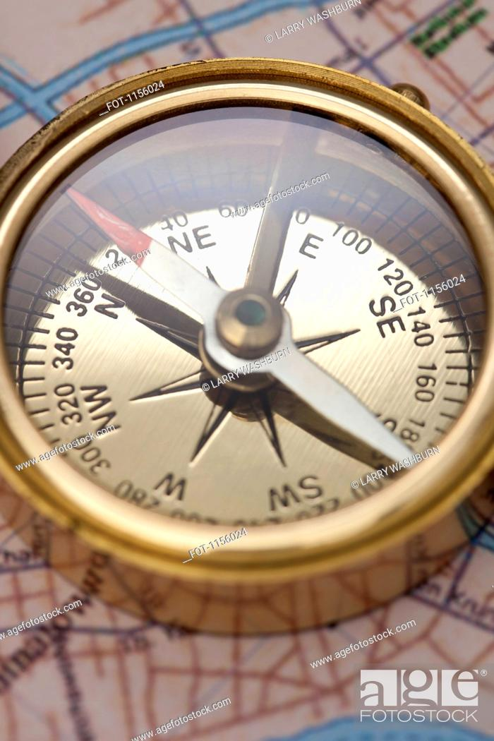 Stock Photo: A compass on top of a road map, focus on compass.