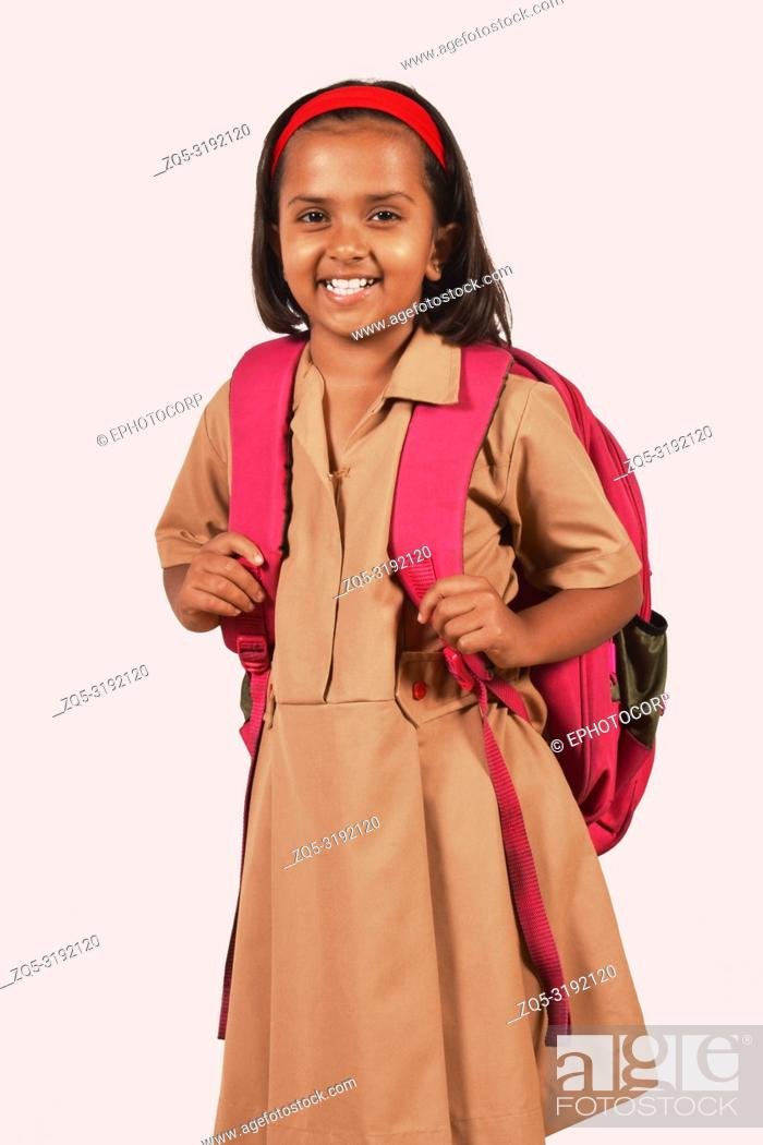 Stock Photo: Little girl in school uniform and bag posing in front of camera. Pune, Maharashtra.