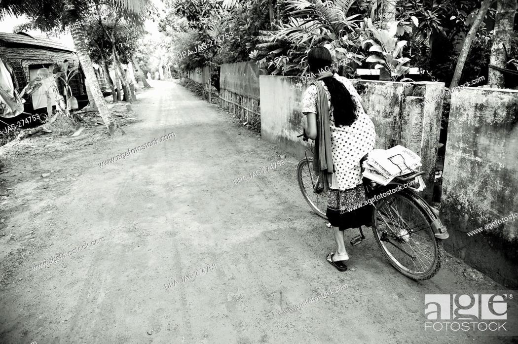 Stock Photo: Girl distributing newspaper on bicycle, Coconut Lagoon Resort, Kumarakom, Kottayam, Kerala, India, Asia.