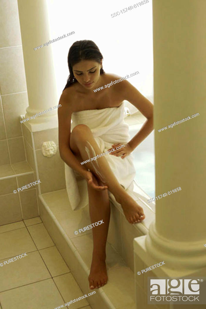 Stock Photo: High angle view of a young woman applying moisturizer on her leg.
