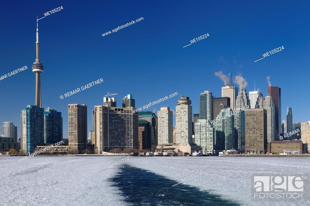 Stock Photo: Wake of a winter ferry to the Toronto Islands with city skyline and ice slush.