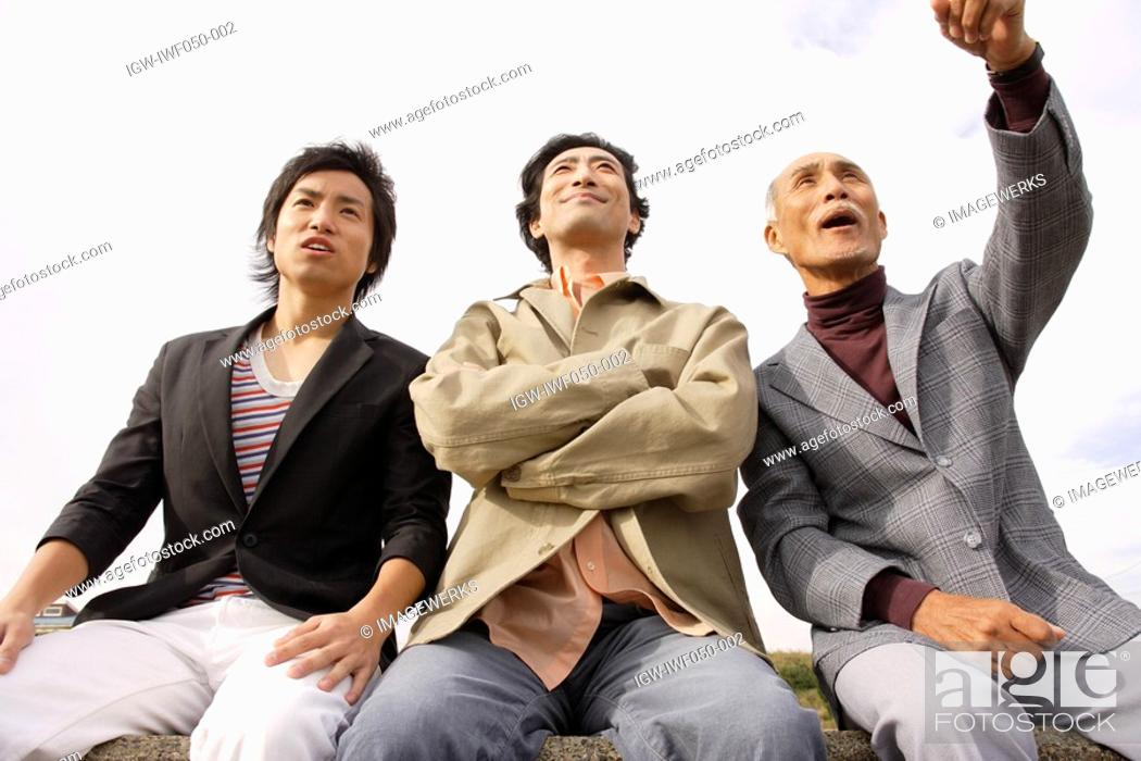 Stock Photo: Young man with father and grandfather pointing out, low angle view.