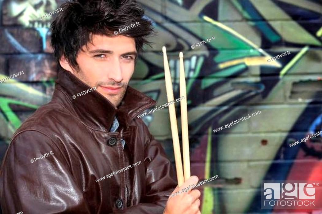 Stock Photo: musician with drumsticks against graffiti wall.
