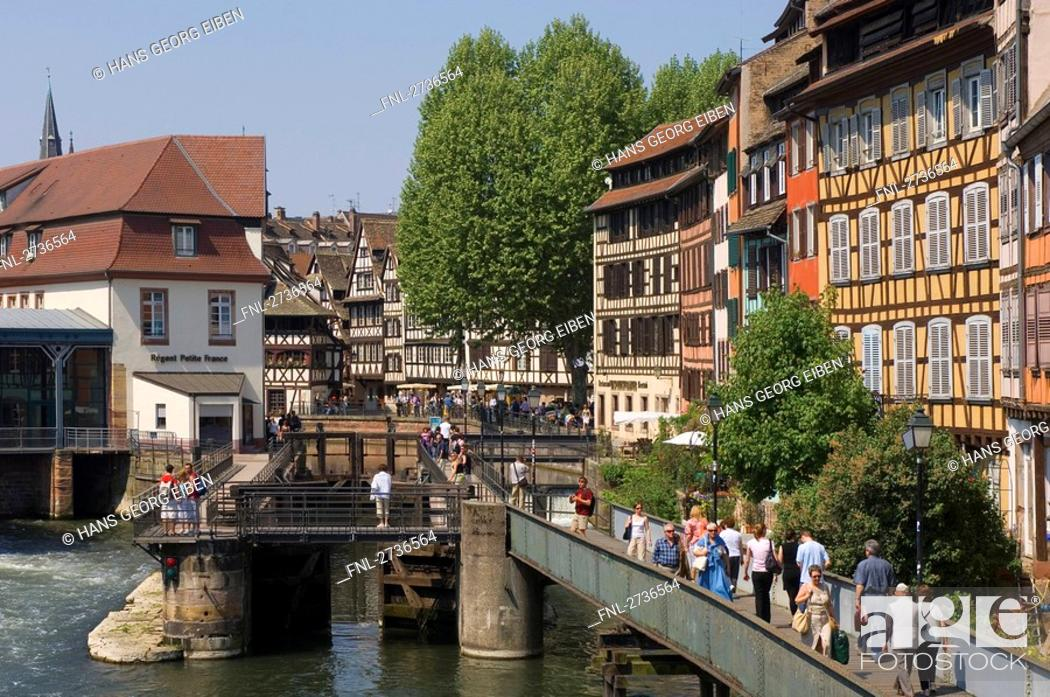Stock Photo: People walking on bridge in front of timber framed houses, Strasbourg, Germany.