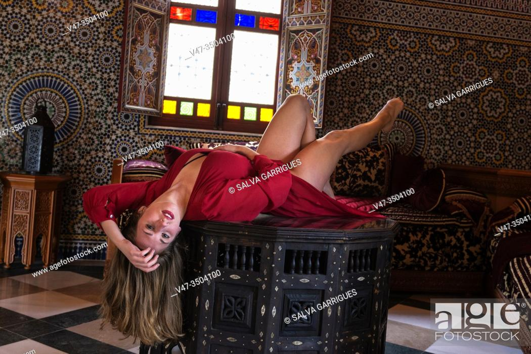 Imagen: Woman in a red dress lying on a table in a salone of an Arab.
