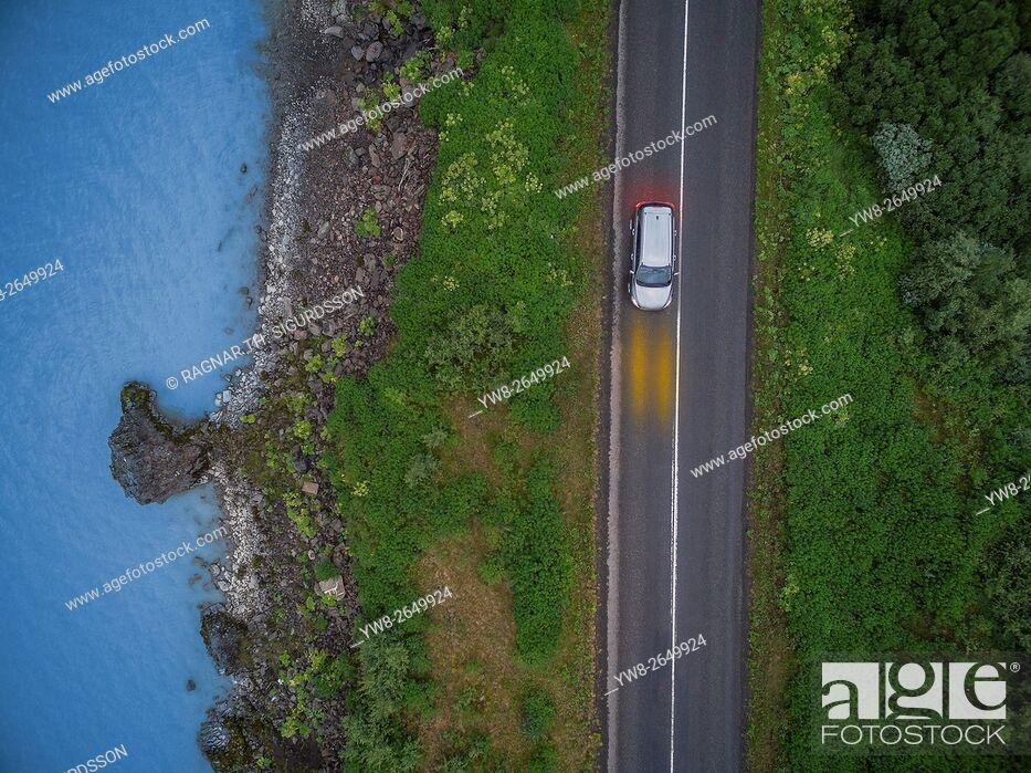 Stock Photo: Aerial view of car on Route One by the Lagarfljot river, Fljotsdalur valley, Egilsstadir, Eastern Iceland. This image is shot using a drone.