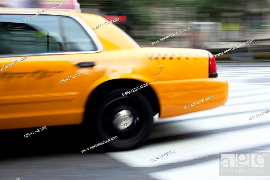 Stock Photo: Blurred view of taxi on city street.