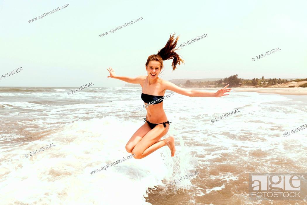Stock Photo: Teenage girl jumping in sea, Goa, India, Asia.