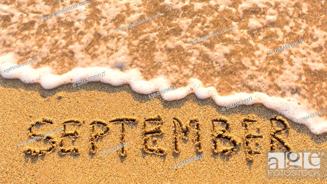 Stock Photo: Inscription SEPTEMBER on a gentle beach sand with the soft wave (months of the year series).
