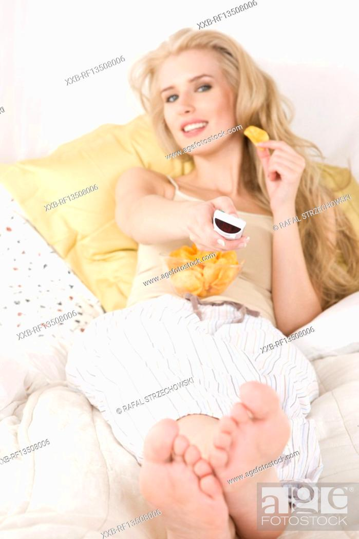 Stock Photo: Woman watching tv in bed.