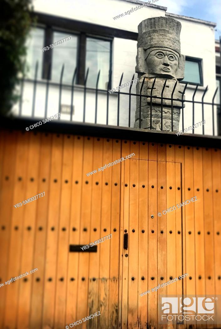 Stock Photo: A reproduction of an sculture of a Atlantean of Tula (Atlante de Tula) decorates a home protected with a fence in Coyoacan, Mexico City, Mexico.