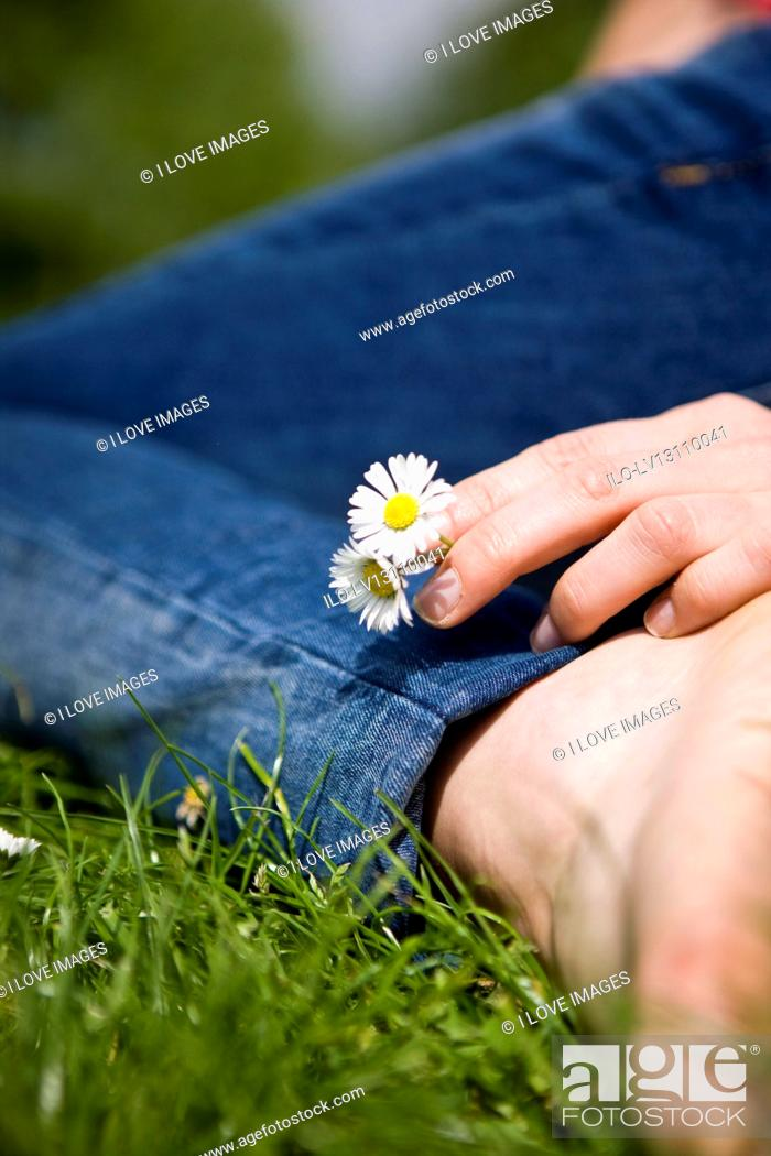Stock Photo: Close-up of a woman holding some daisies.