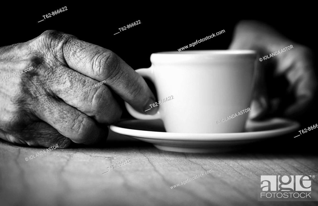 Stock Photo: Time for coffee  Hands of elderly woman holding a cup.