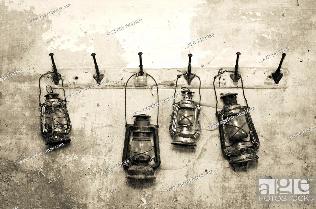 Stock Photo: Oil lamps hanging disused in a garage in Radbourne, Derbyshire.