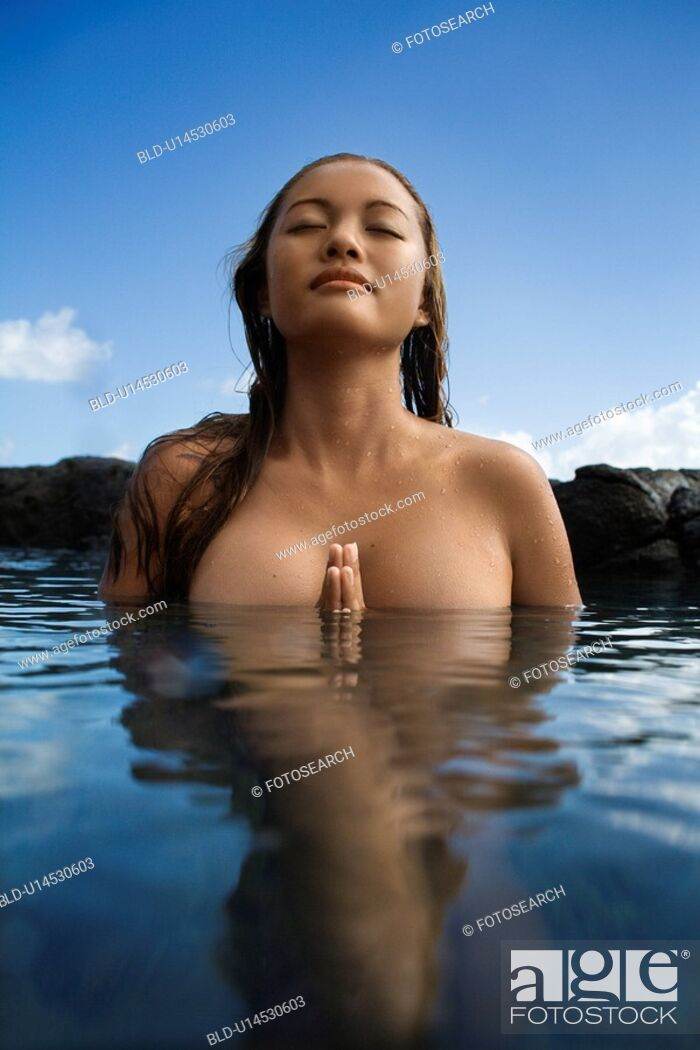 Photo de stock: Young Asian nude woman partially submerged in water with eyes closed and hands together.