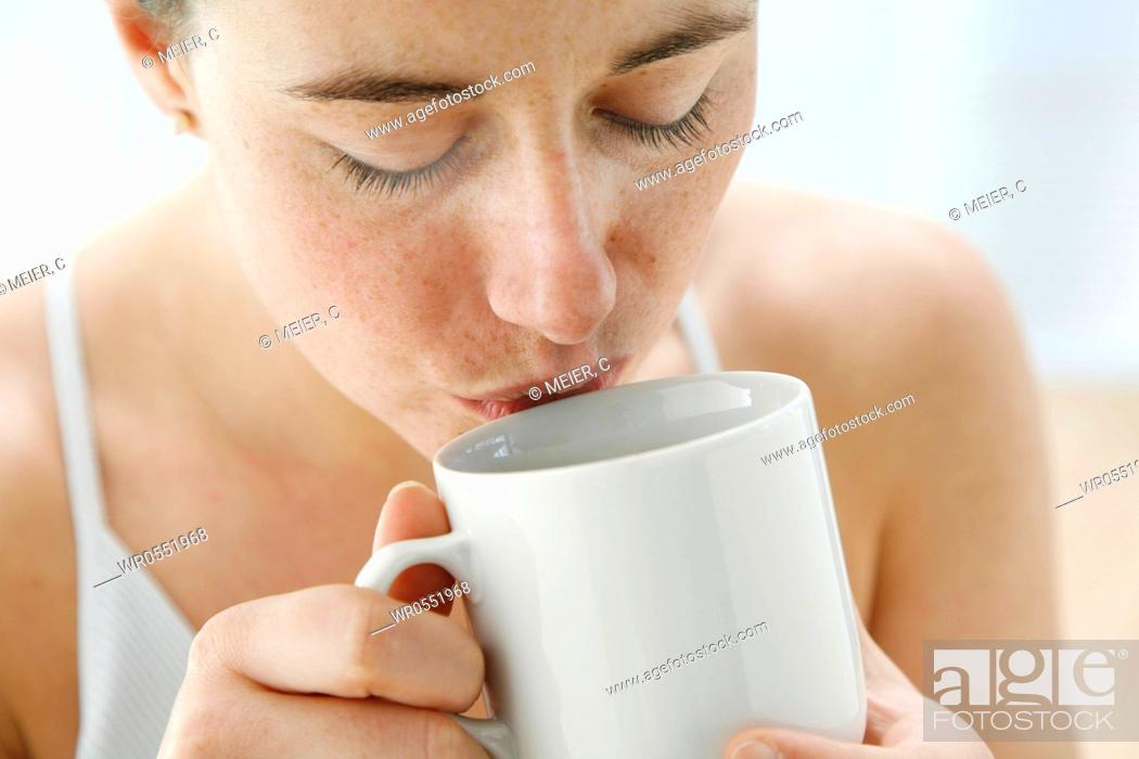 Imagen: portrait - young woman is drinking tea out of a tea cup.