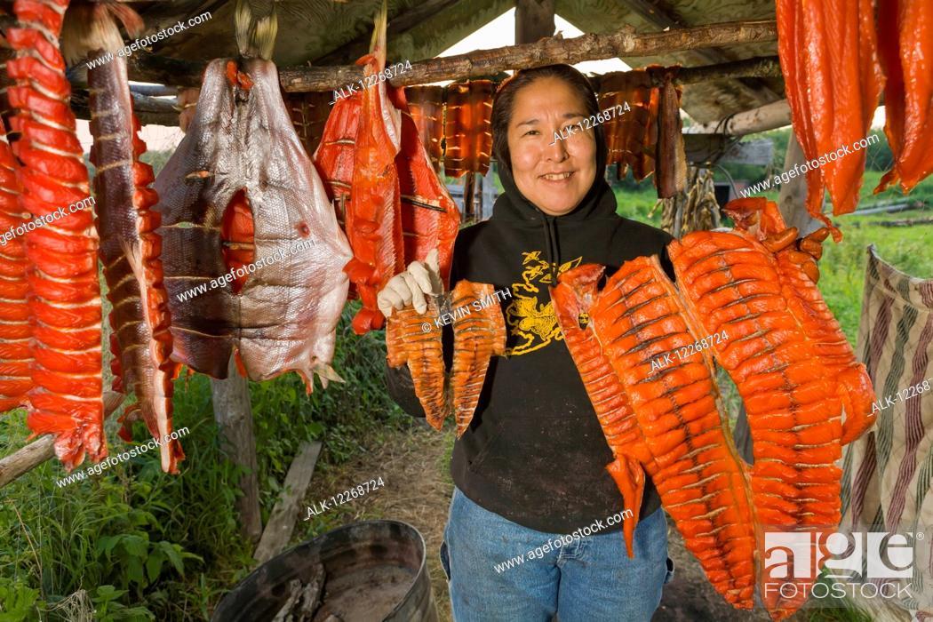 Stock Photo: Native Yup'ik eskimo woman showing a very small and very large subsistance caught King Salmon, Tuluksak, Southwestern Alaska.