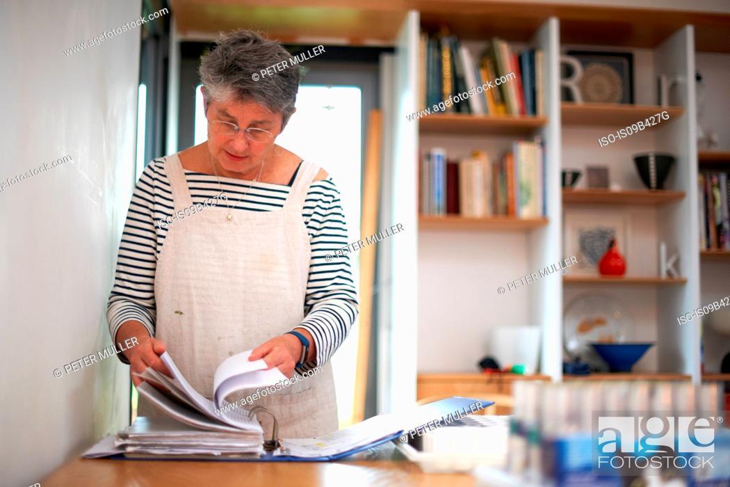 Stock Photo: Senior woman in kitchen, looking through file.