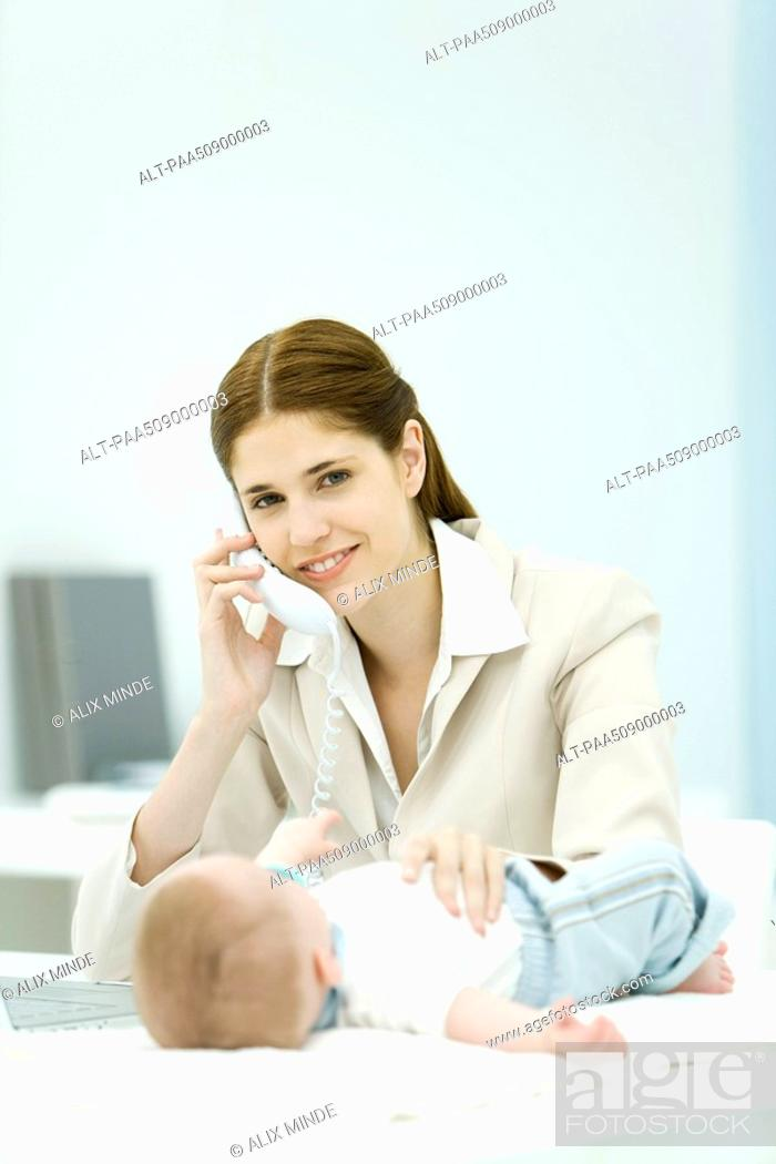 Stock Photo: Professional woman using phone in office, smiling at camera, baby lying on desk.