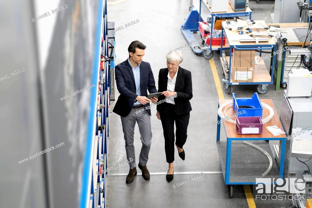 Stock Photo: Businessman and senior businesswoman with tablet walking in a factory.