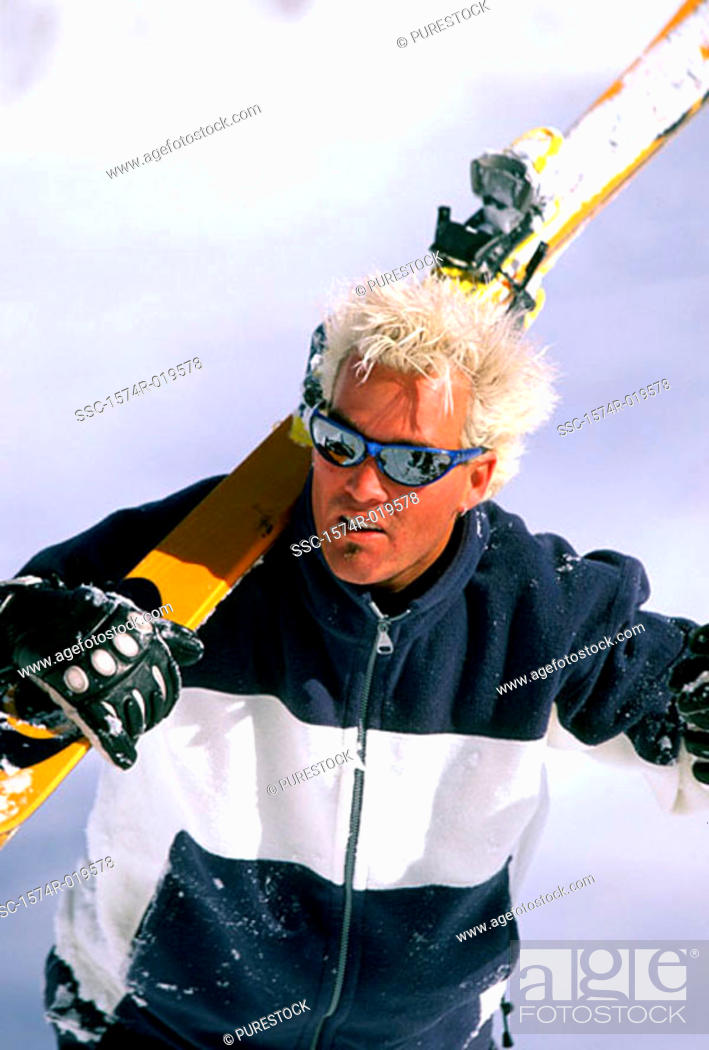Stock Photo: Close-up of a young man carrying a ski on his shoulders.