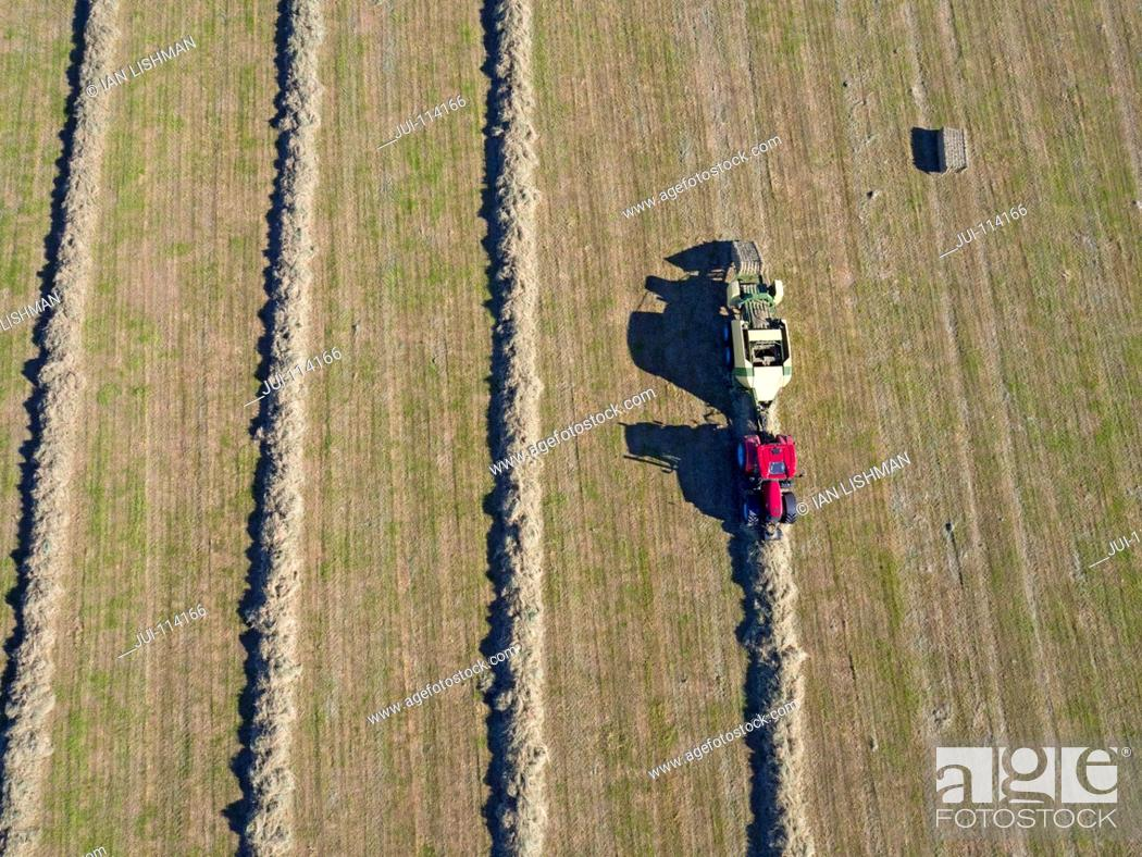 Stock Photo: Aerial View Of Tractor Baling Hay In Field.