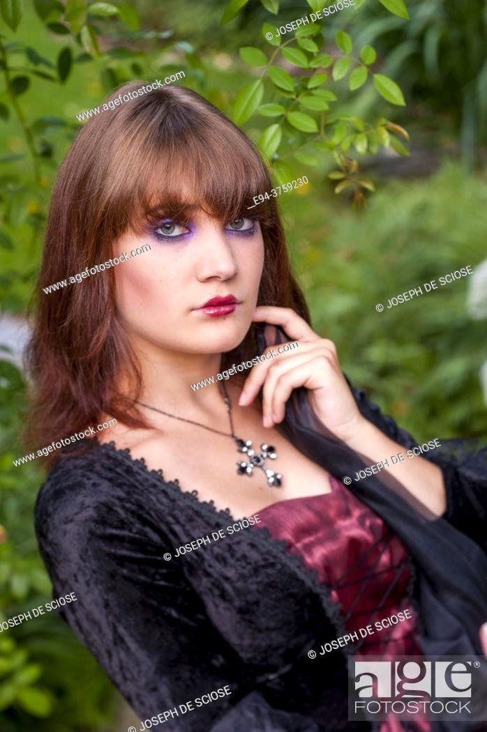 Photo de stock: An 18 year old brunette woman wearing a costume in a garden setting looking directly at the camera.