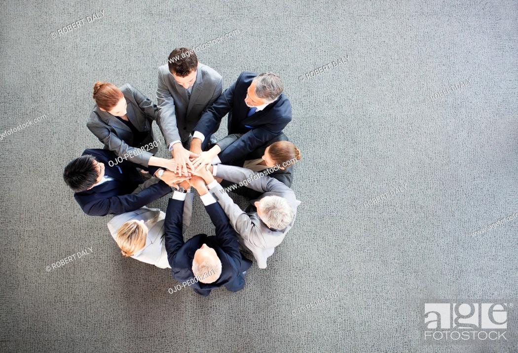 Stock Photo: Business people stacking hands in circle.