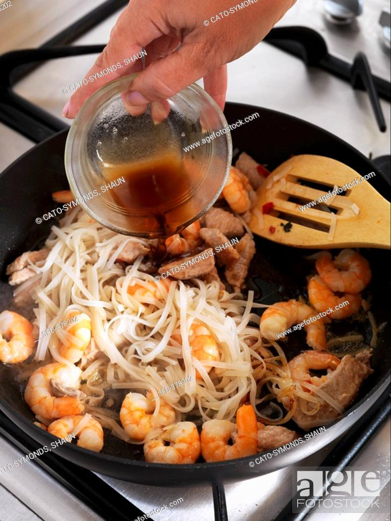 Stock Photo: Adding fish sauce to a pan of shrimps and glass noodles.
