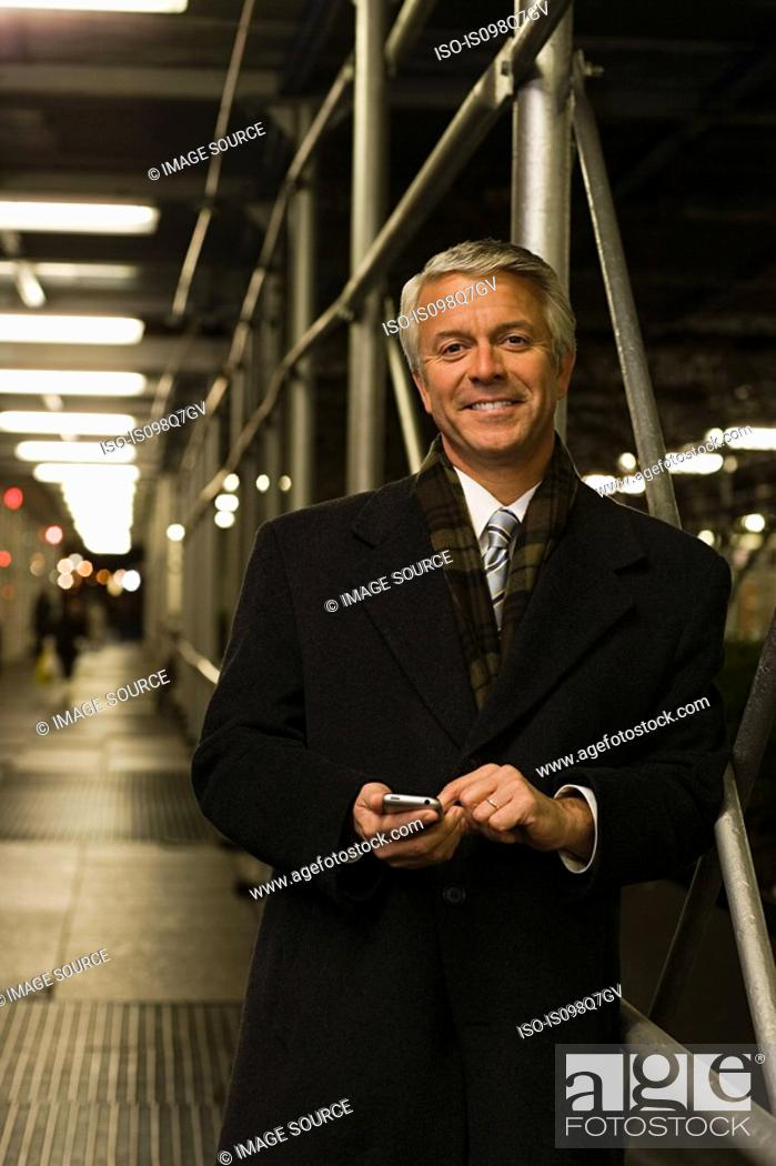Stock Photo: Smiling mature businessman text messaging.