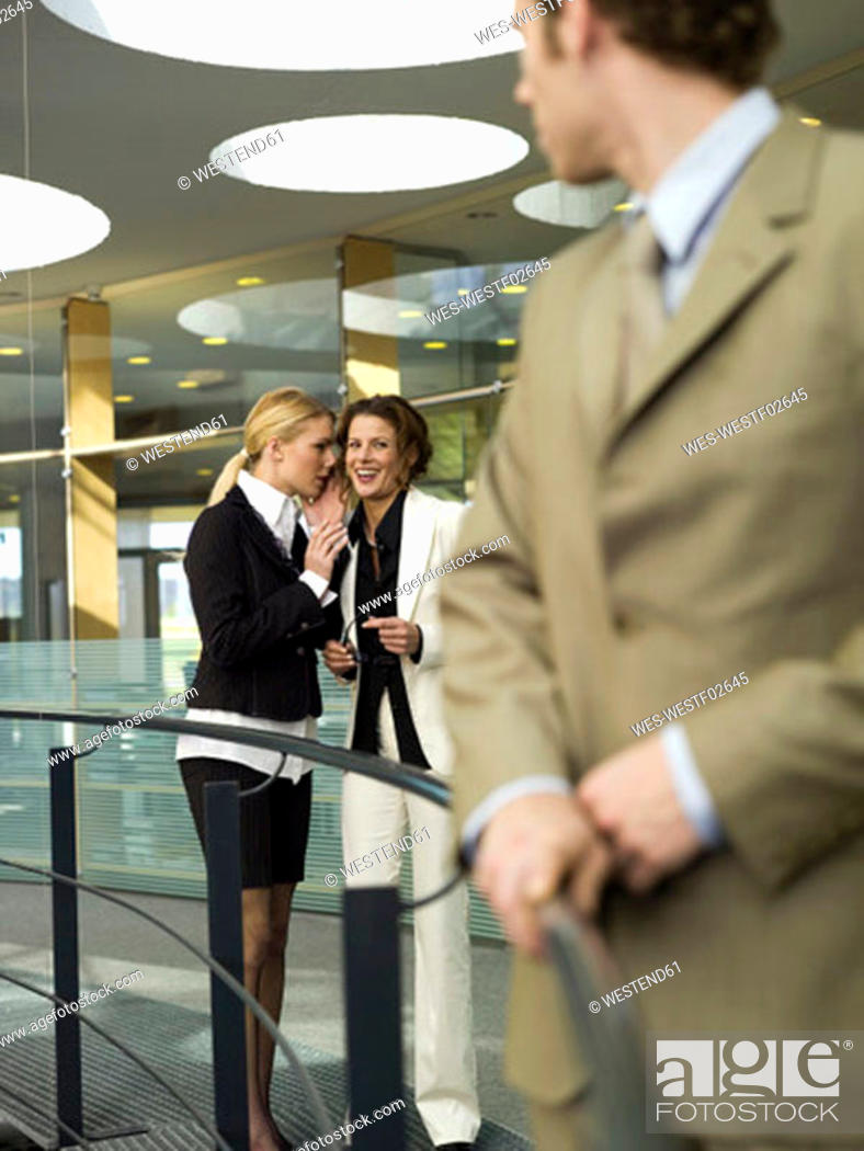 Stock Photo: Women talking behind back of young businessman.