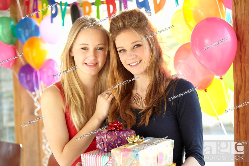 Stock Photo: Two teenage girls sharing gifts at birthday party.