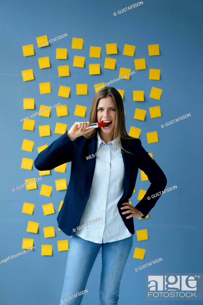 Imagen: Yong businesswoman standing in front of wall, full of yellow sticky notes, biting marker pen.