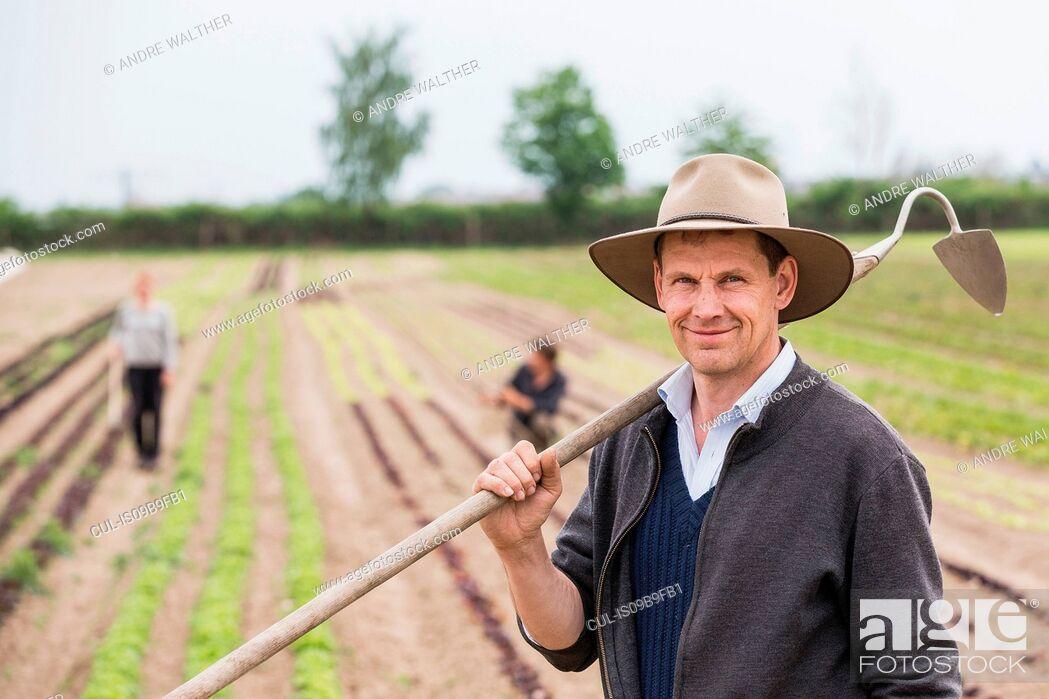 Stock Photo: Portrait of farmer in field with hoe.