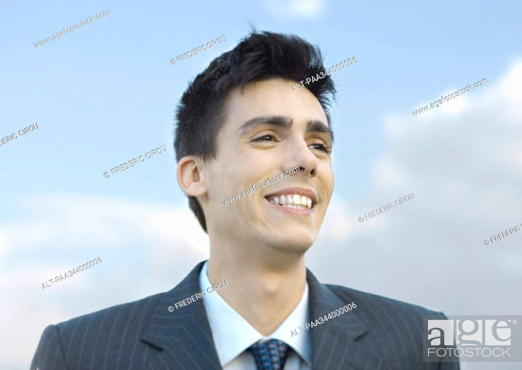 Stock Photo: Young businessman smiling, portrait.