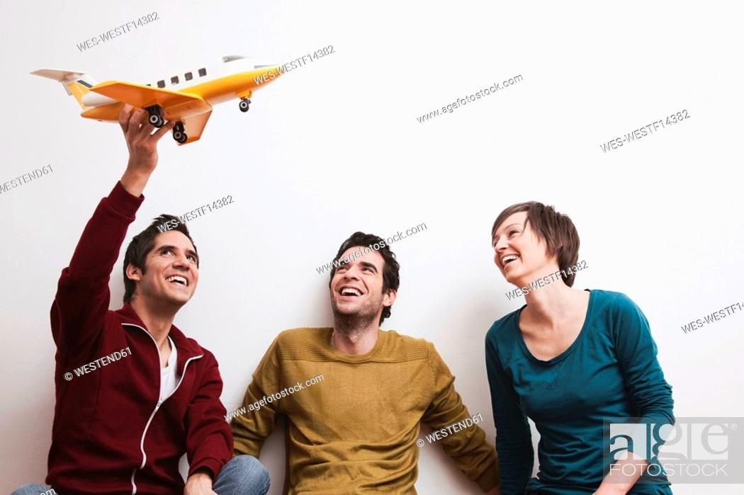 Stock Photo: Men and women playing with toy aeroplane, smiling.
