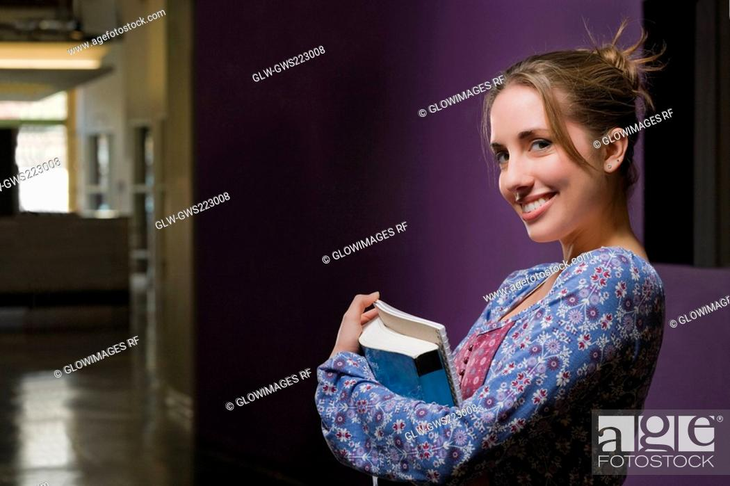 Stock Photo: Portrait of a young woman holding textbooks and smiling.