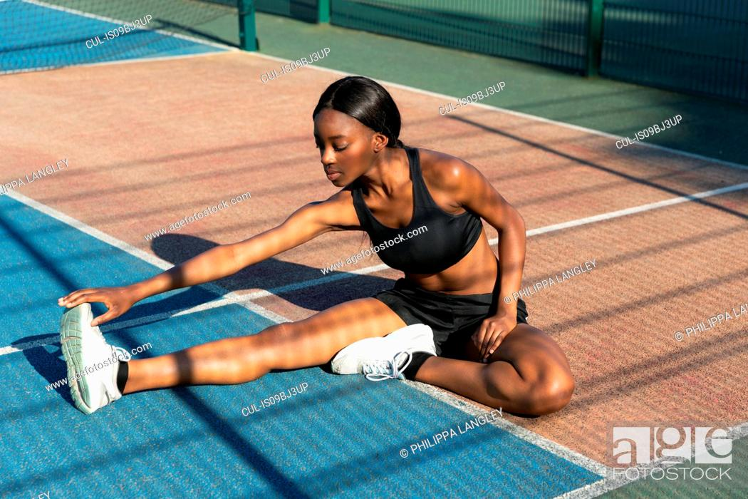Stock Photo: Young woman stretching in sports court.