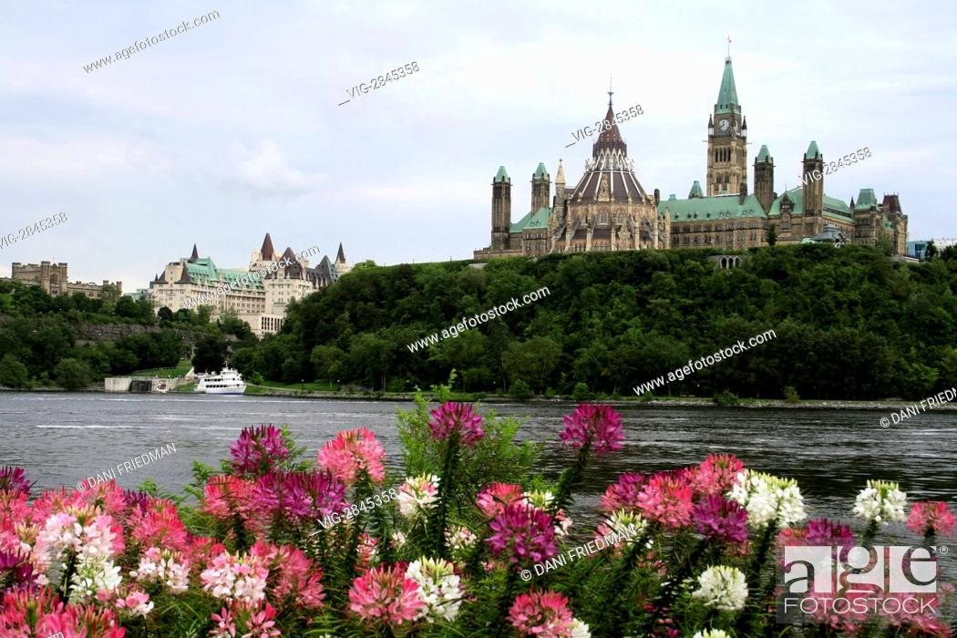 Stock Photo: CANADA, GATINEAU, 10.08.2008, A scenic view of Ottawa and the Canadian Parliament Buildings with colourful flowers as seen from across the river in Gatineau.