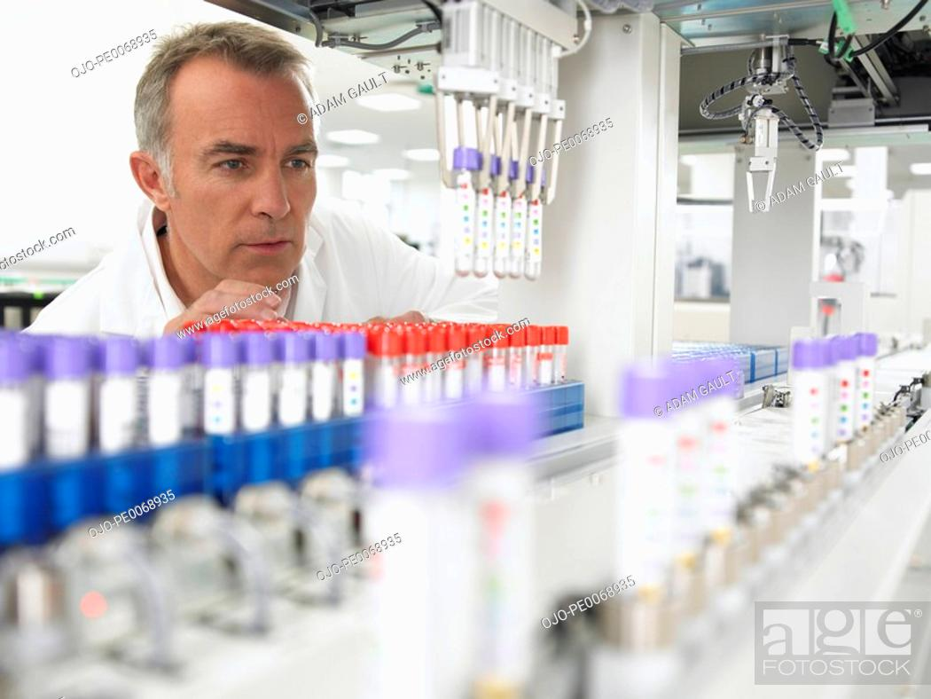 Stock Photo: Scientist examining test tubes in laboratory.