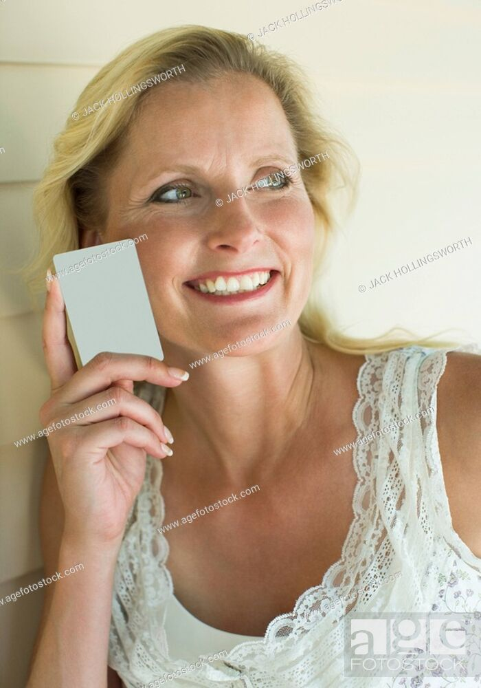 Stock Photo: Close-up of a mature woman holding a credit card and smiling.