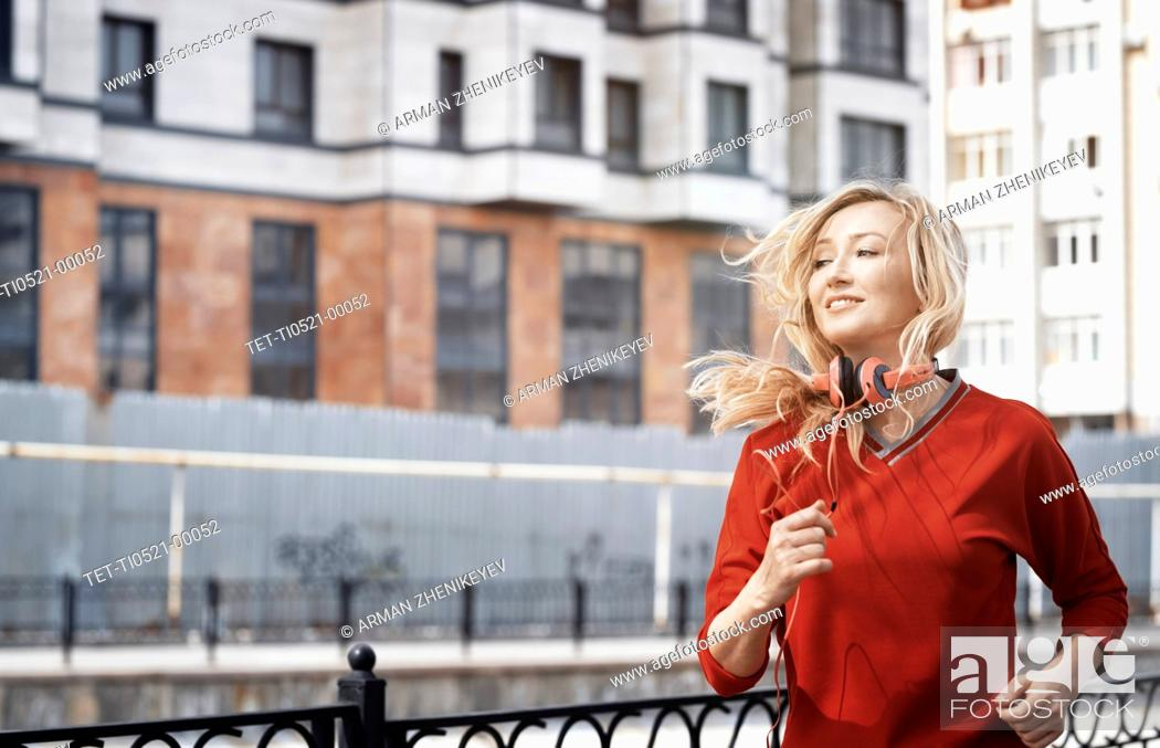 Stock Photo: Woman with headphones jogging in city.